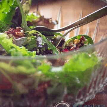 A green salad with candied walnuts avocado and pomegranate in a glass bowl
