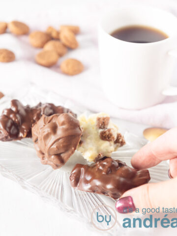 Three different kinds of pepernoten chocolate with pepernoten around them and two cups of coffee