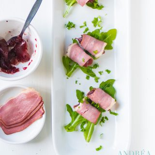 three amuse-bouche with duck breast filet, cranberry compote on a bed of arugula