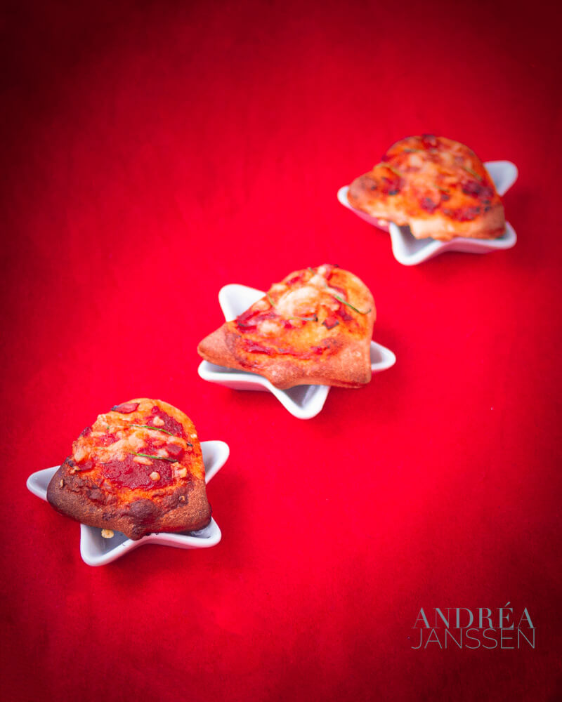 three Christmas pizza on a small plate on a red background