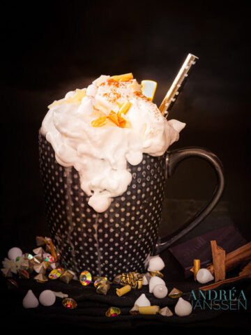 a cup of Hot chocolate with vanilla and herbal liquor with golden props