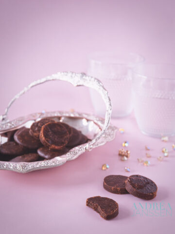 A silver platter with chocolate fondant. Some fondants in the front and all in a pink background