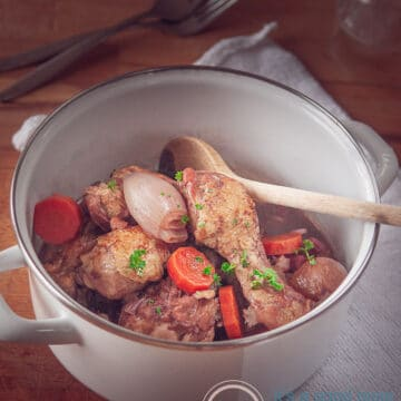 Coq au vin in a white pan on a wooden table