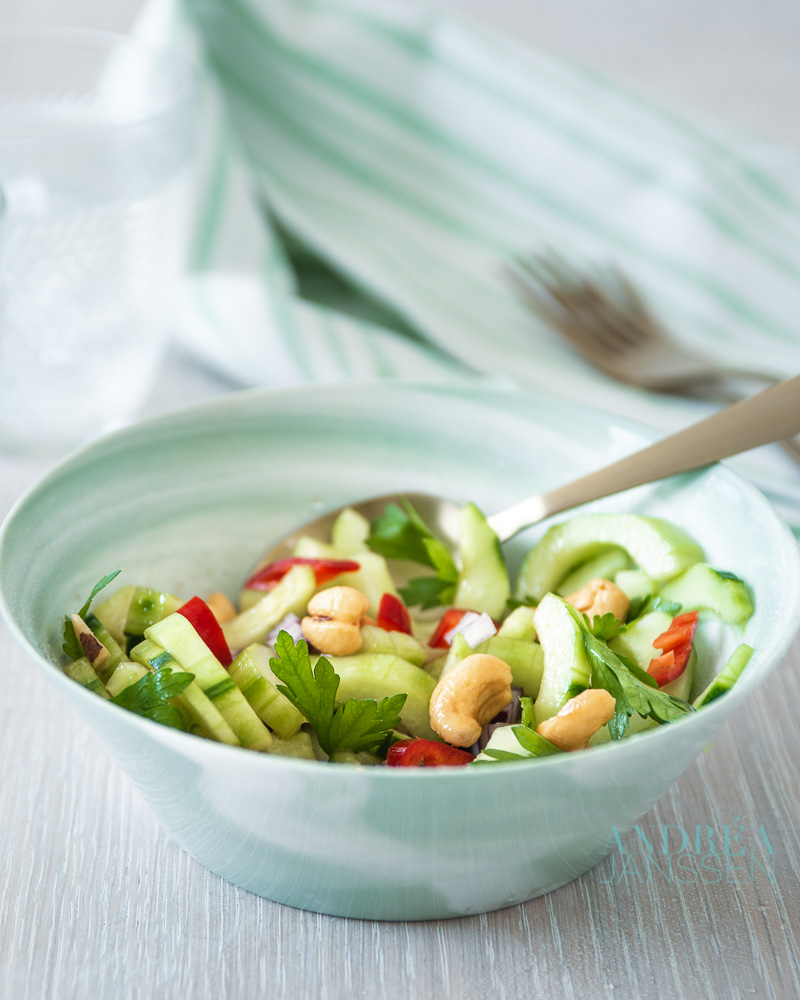 a green bowl with Spicy cucumber salad