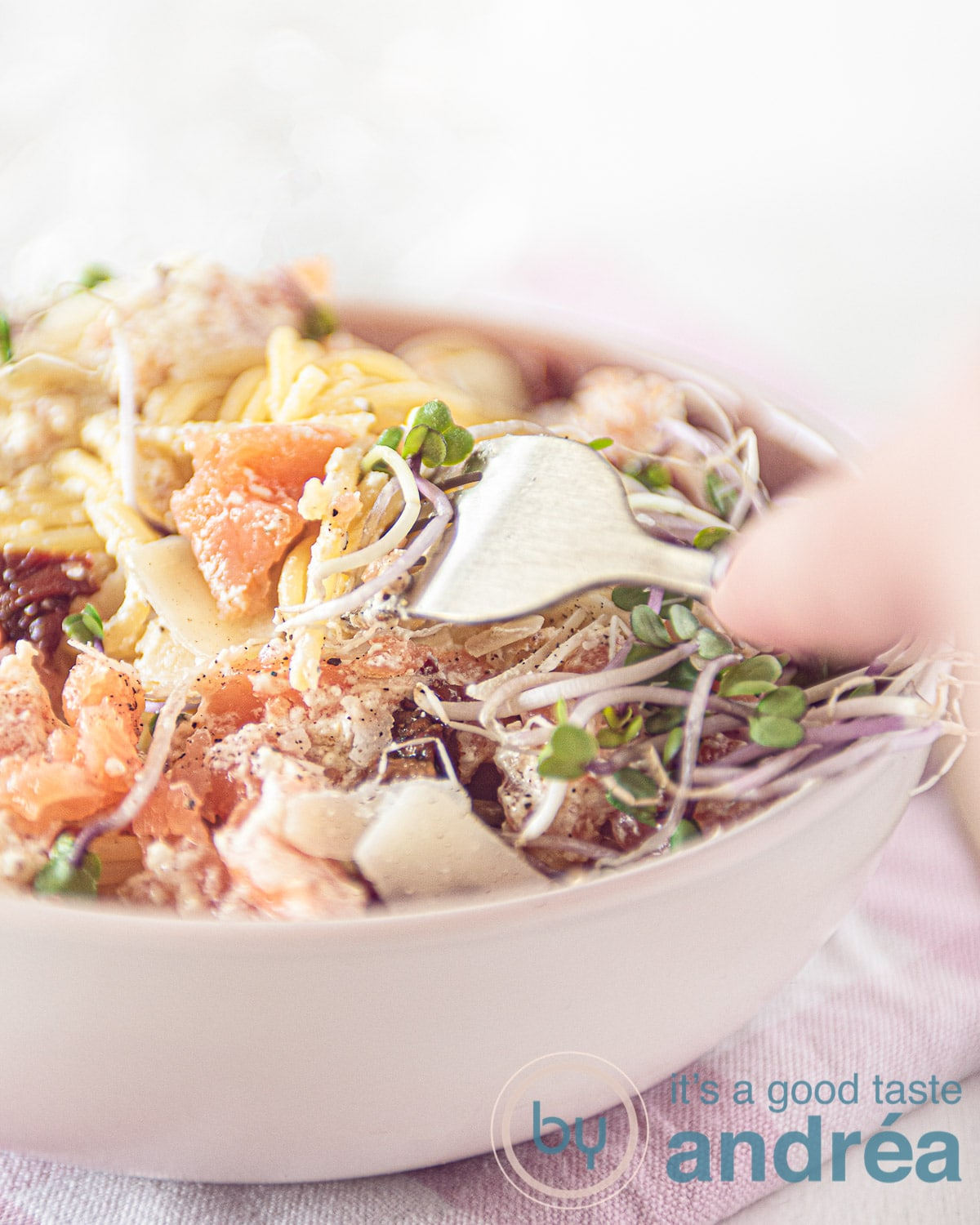 a white plate with spaghetti with smoked salmon and sun-dried tomatoes