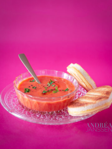 a glass bowl with tomato soup and grilled cheese sandwiches on a pink background