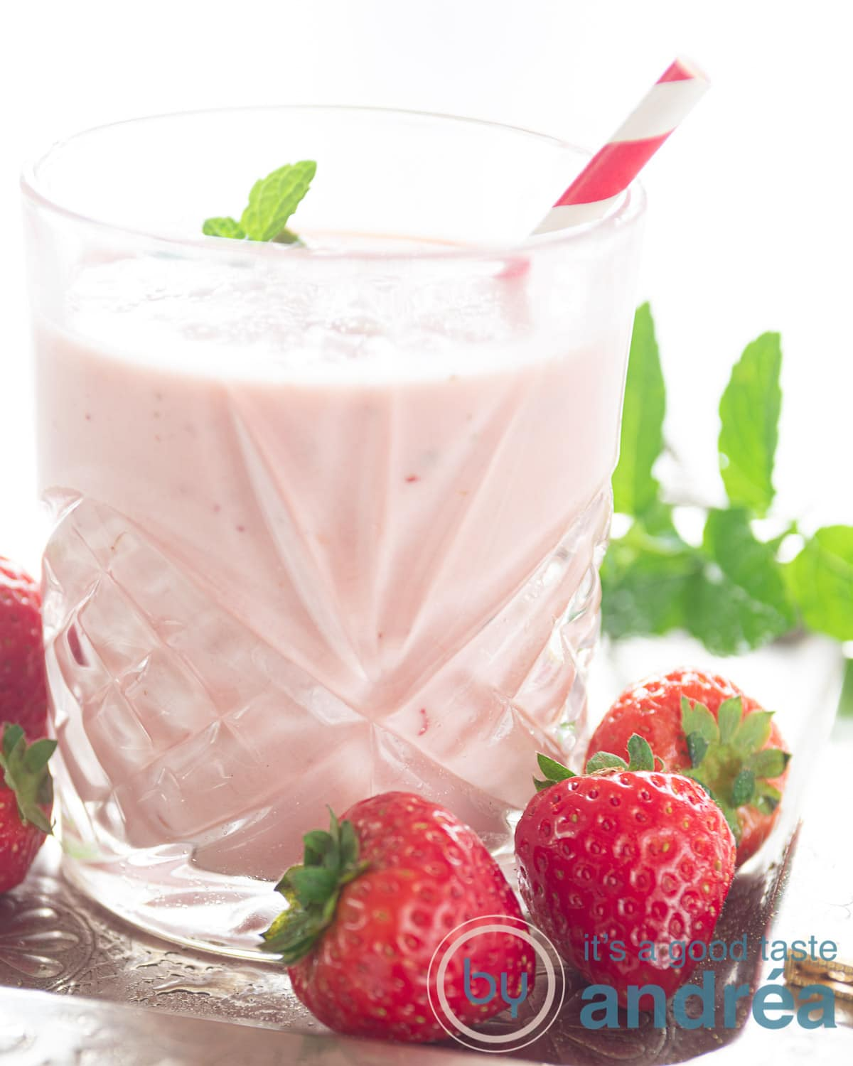 On the left a glass with strawberry smoothie with orange. Some fresh strawberries and mint are on the right side.