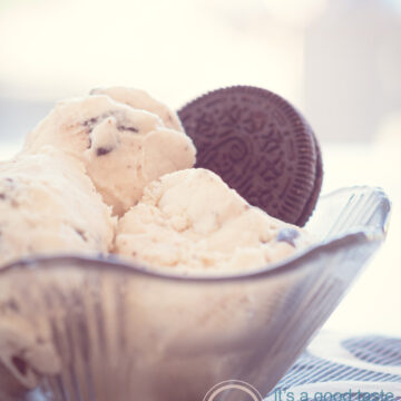 a black glass bowl with three scoops of Oreo ice cream and a cookie
