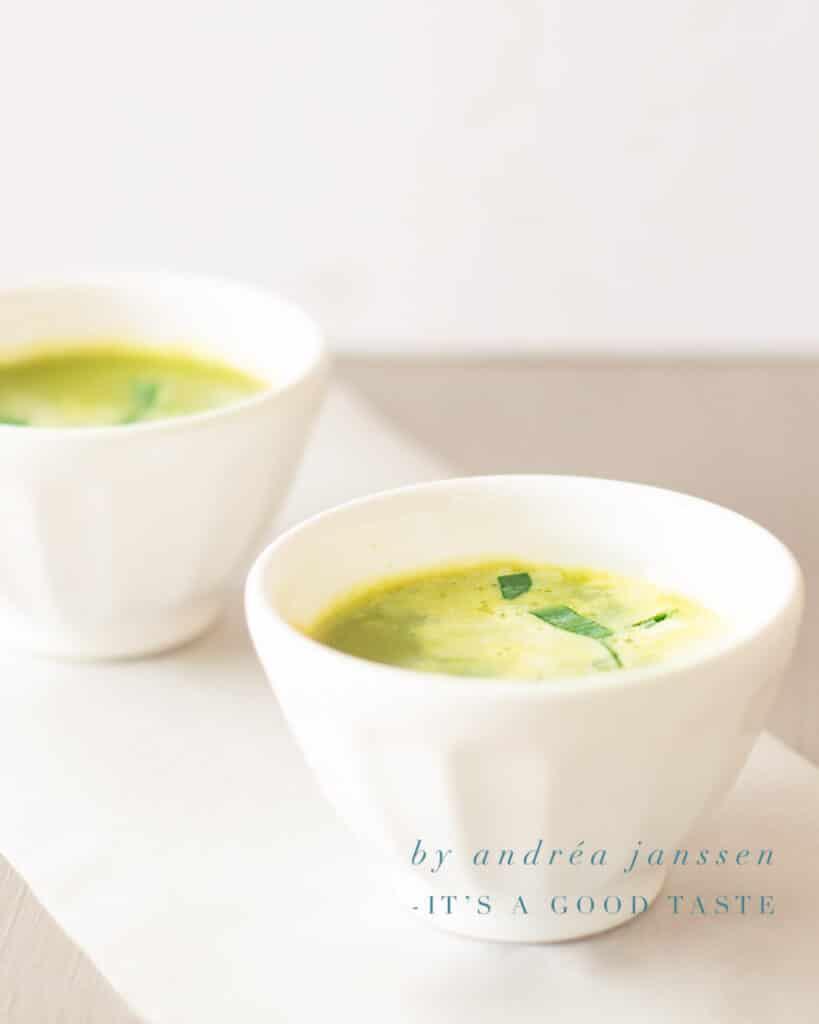 twee witte kommetjes met een soepje van doperwtjes