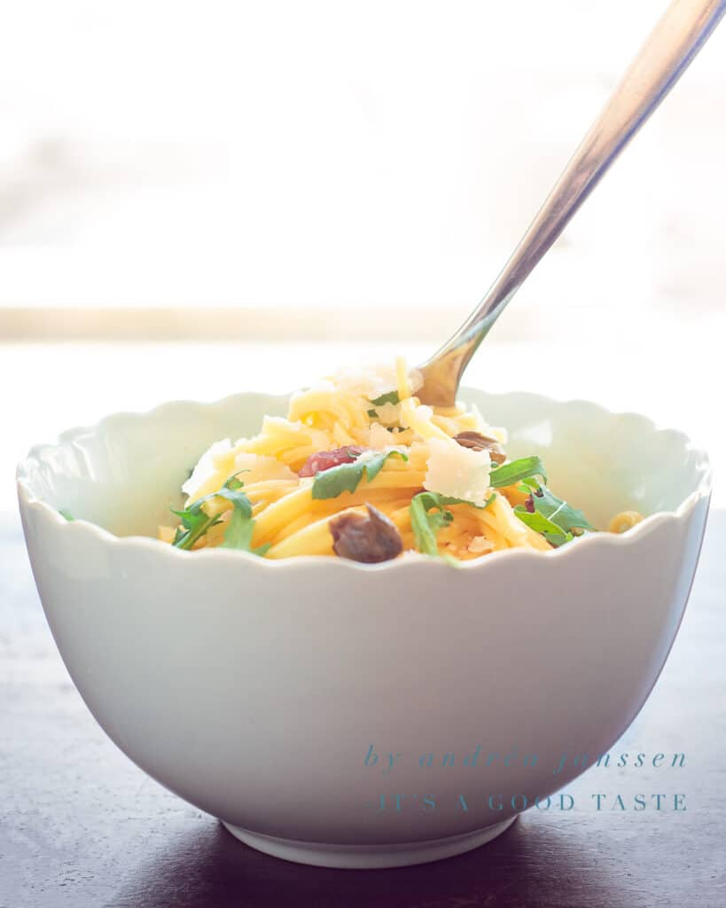 a white bowl with spaghetti, arugula and capers