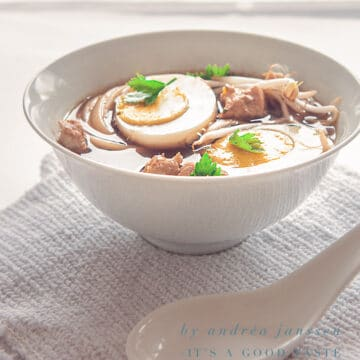 a white bowl filled with Ramen Noodle soup with an egg