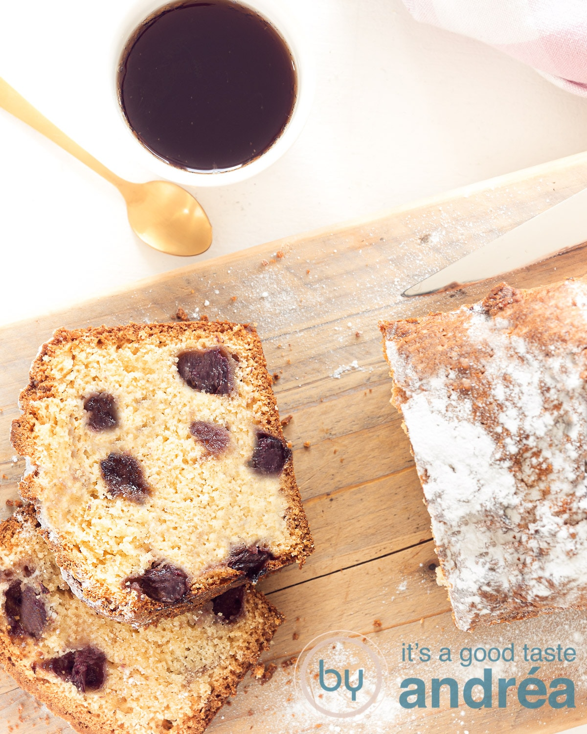 Photo from above. Cake on a wooden board. Cut two slices. At the top a cup of coffee with a golden spoon.