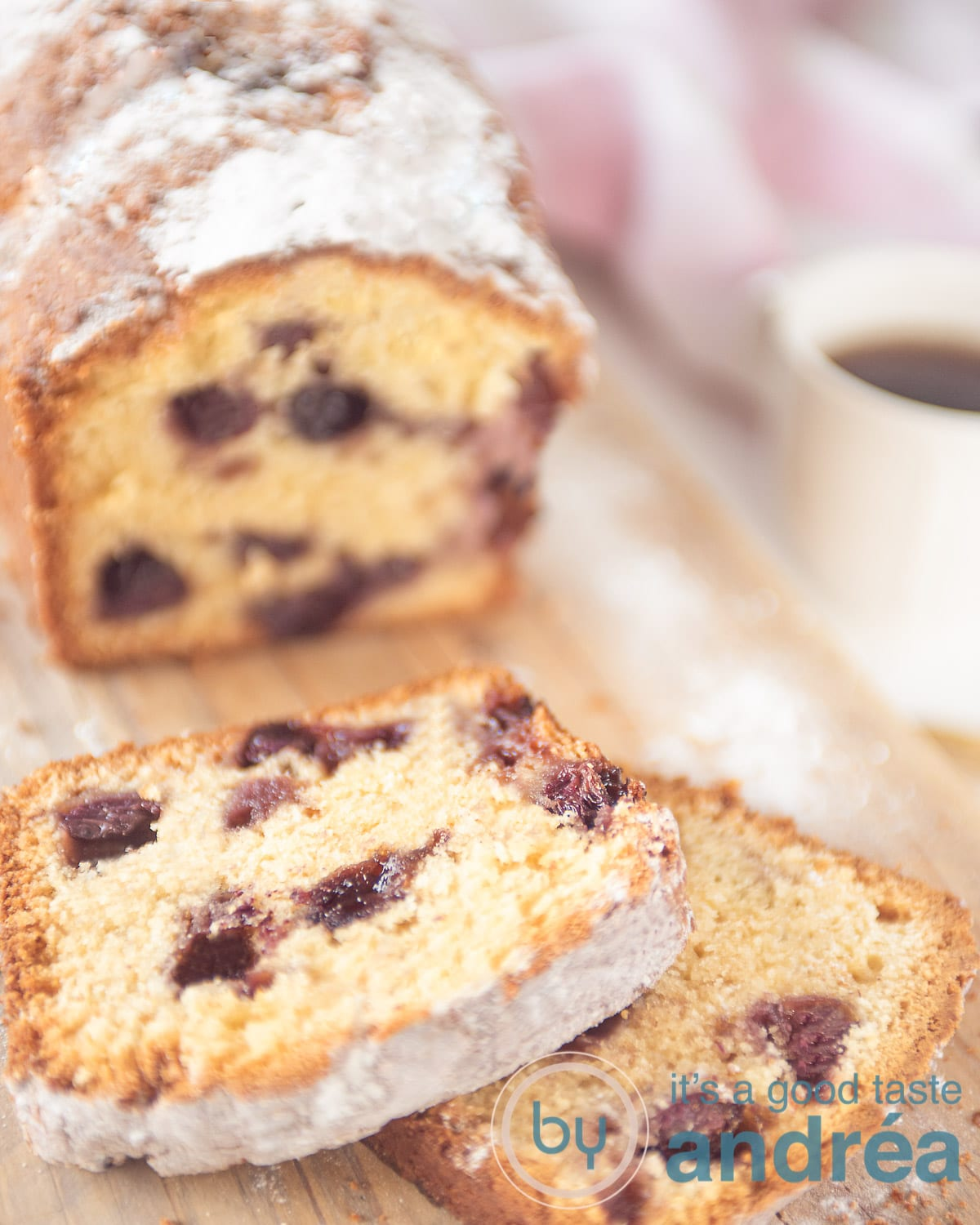 A wooden board with a cake with blueberries. Two slices off. A cup of coffee on the right