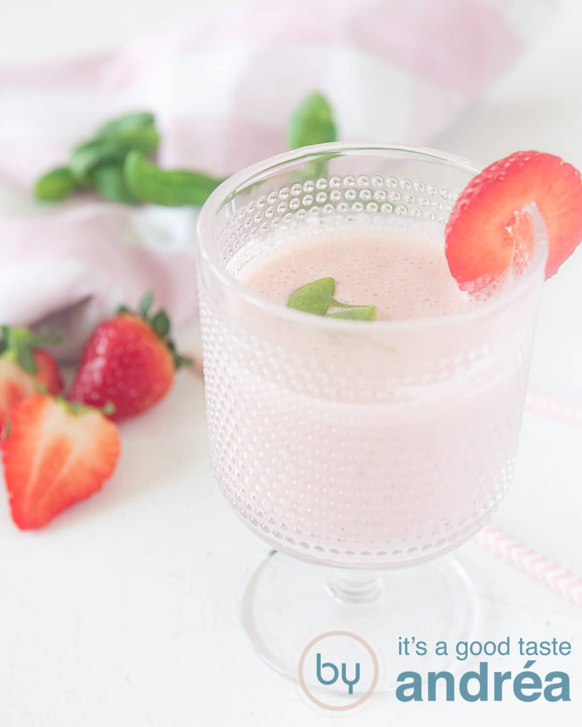 A glass with strawberry yogurt smoothie. Some strawberries and. basil in the background