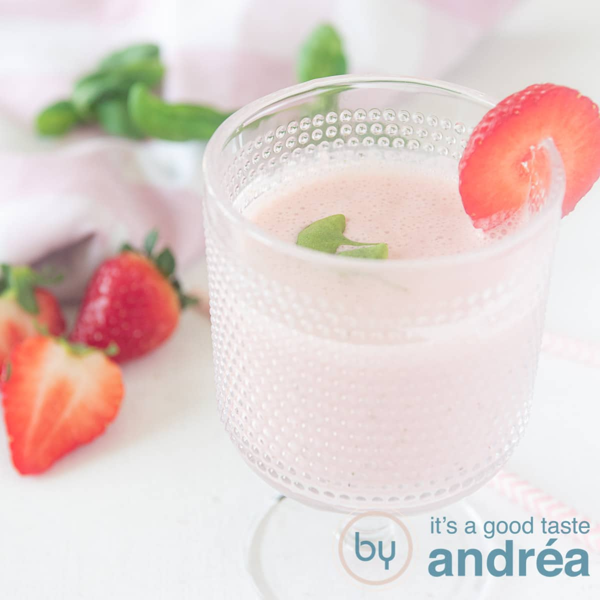 a square photo with a glass filled with a smoothie with strawberries and basil