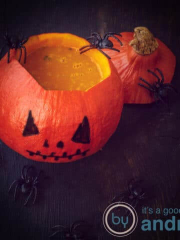 an orange pumpkin filled with pumpkin soup and spiders