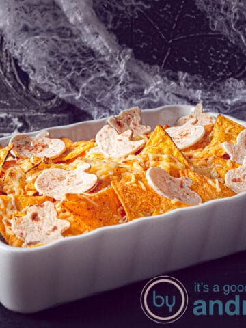 a square photo of a chicken casserole topped with nachos and tortilla's