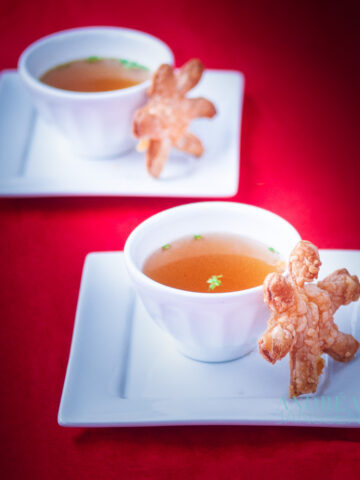 two bowls with vegetable stock and puff pastry cheese stars