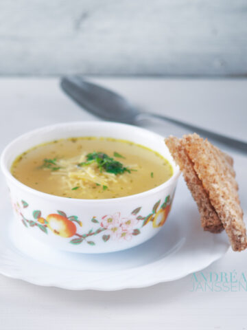 a bowl with noodle soup with herbs and a slice of bread