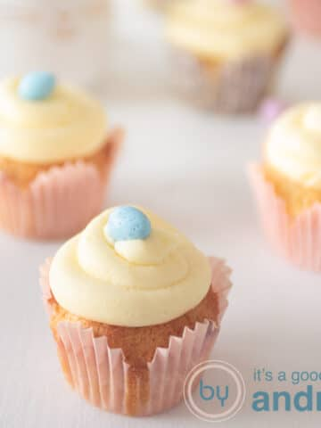 a square photo of four easter cupcakes which are topped with butter cream