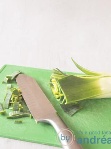 A leek on a green cutting board, some slices of leek on the left. A knife in the middle.