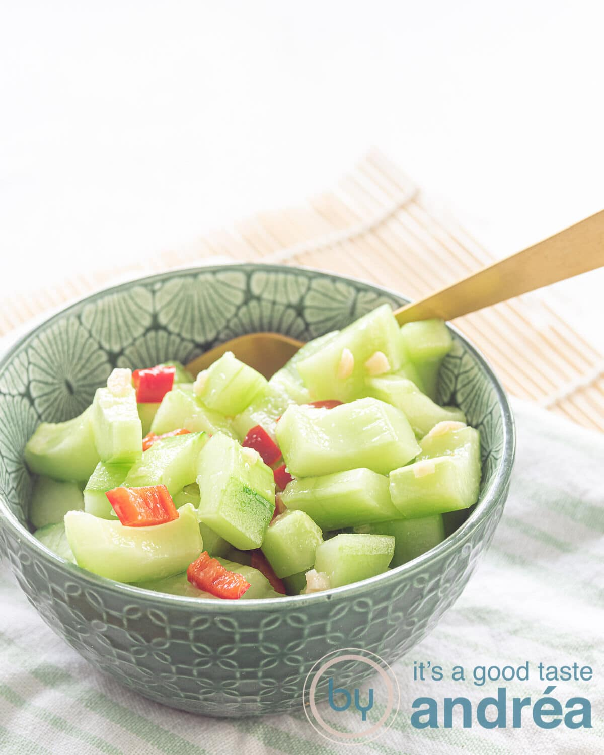 a green bowl with cucumber, pepper and garlic