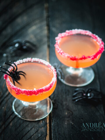 two Halloween cocktails with Passoa, Malibu and Orange juice and some spiders across the picture