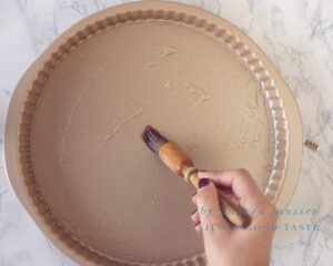 Brush the quiche form with oil