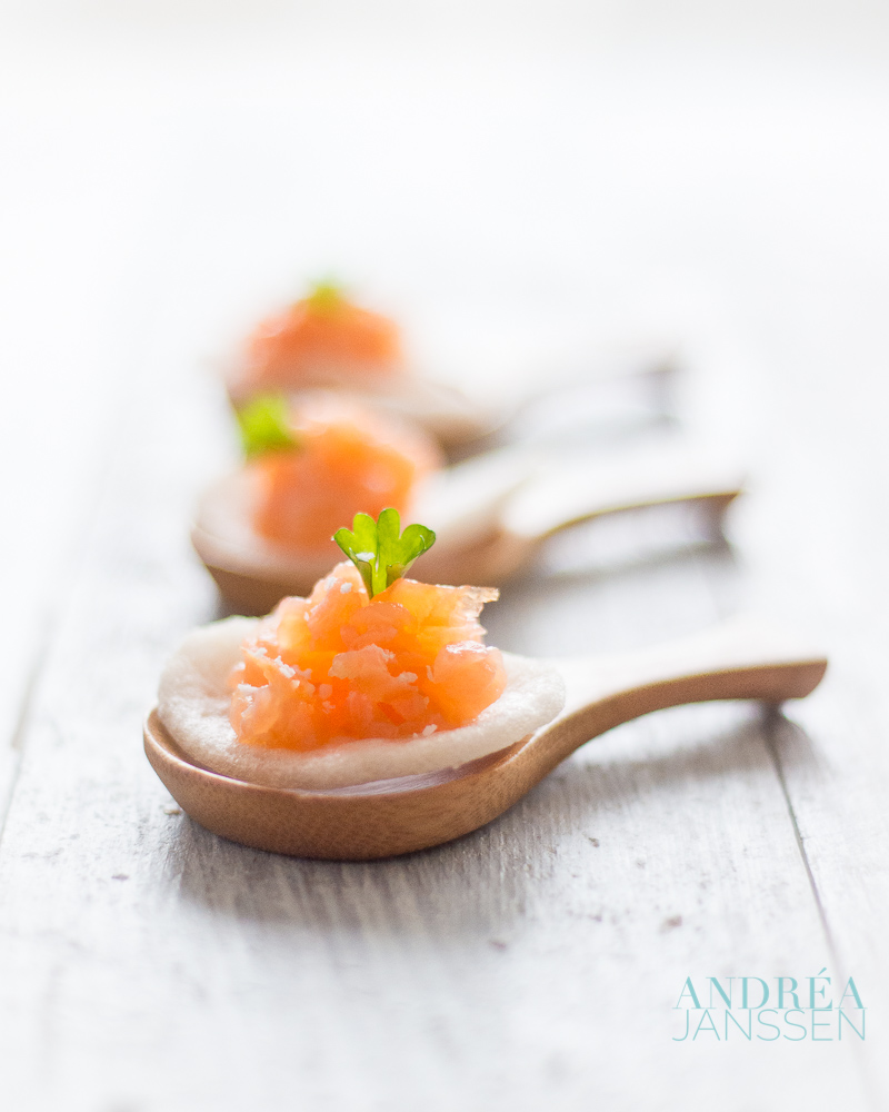 three bamboo spoons topped with a prawn cracker with smoked salmon