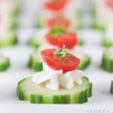 a plate with cucumber slices topped with herb cream cheese and a half cherry tomato