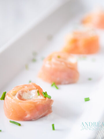 a white plate with 4 smoked salmon spirals with cream cheese