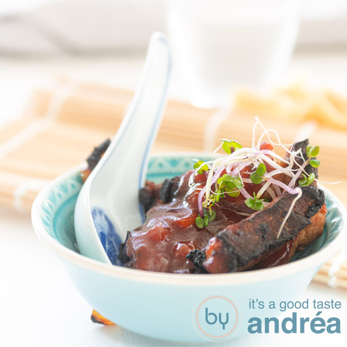 square photo of babi pangang in a blue bowl