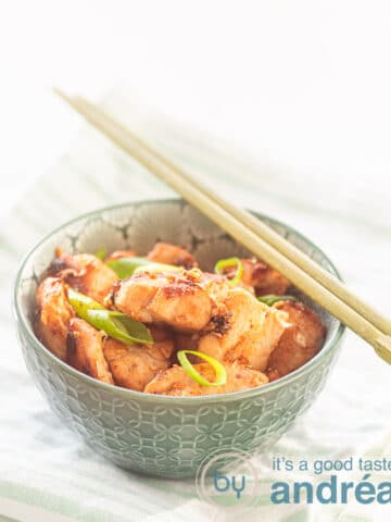 A green bowl of chicken with 4 flavors seasoned. Two chopsticks are on top of it. The bowl is on a green white striped towel