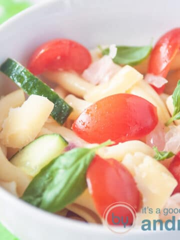 a square photo with a white bowl with pasta, basil, tomatoes and onions