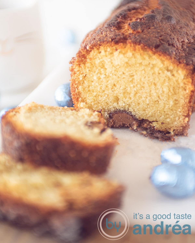 Een foto van een cake gevuld met paaseitjes op een witte plank. Een kopje thee in de linker achterzijde