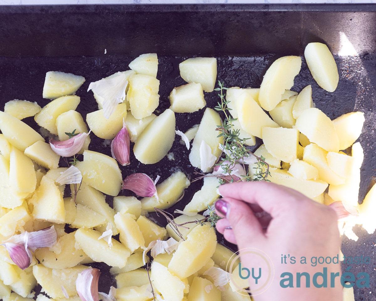 Verdeel de aardappelen met de knoflook en tijm over de bakplaat