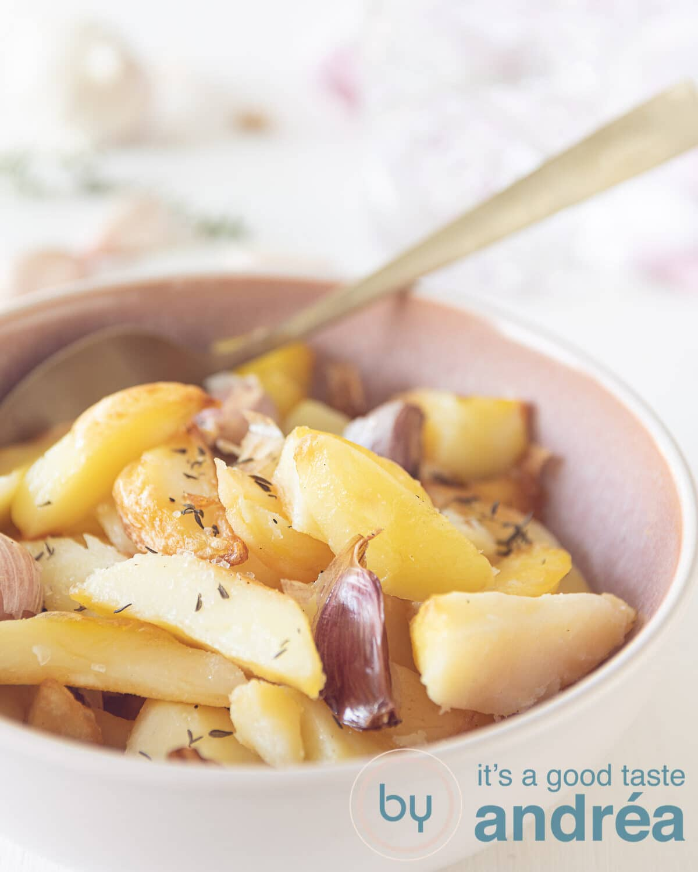 oven gebakken aardappelen met knoflook en tijm in een roze schaaltje.