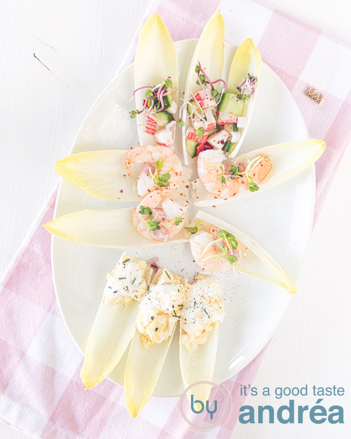 a white plate with chicory boats filled with crab, shrimp and egg salad