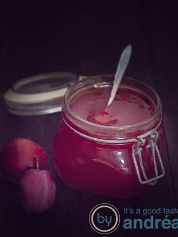 A jar of plum jam with vanilla on a dark background. Two plums on the left