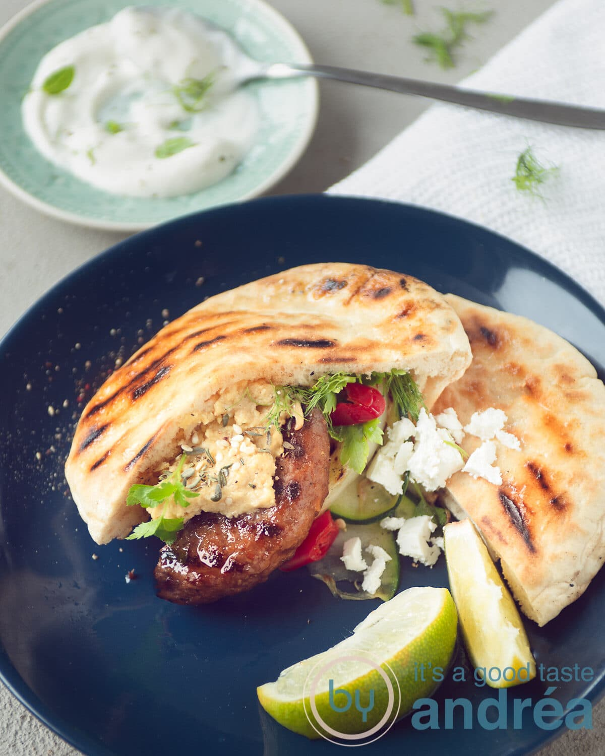 A blue plate with grilled vegetables, hamburger and feta cheese.