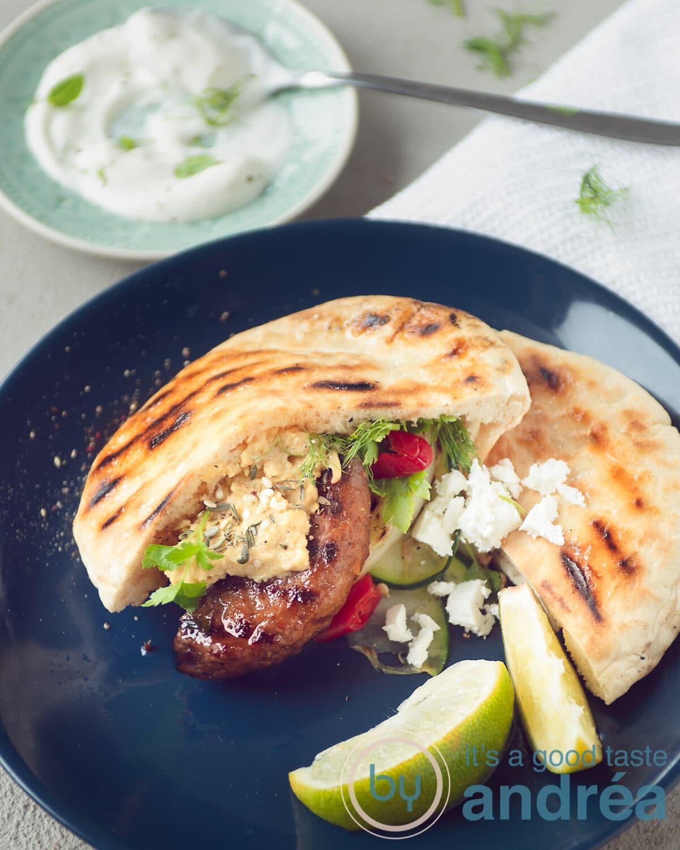 Een blauw bord met een pita broodje gevuld met runderhamburger, feta en gegrilde groenten