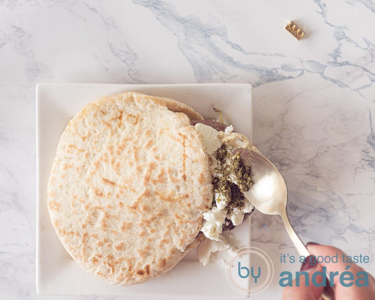 Een pitabroodje met hamburger, feta en za'atart