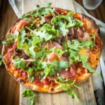 Pizza Italian de luxe with parmaham, arugula and pine nuts