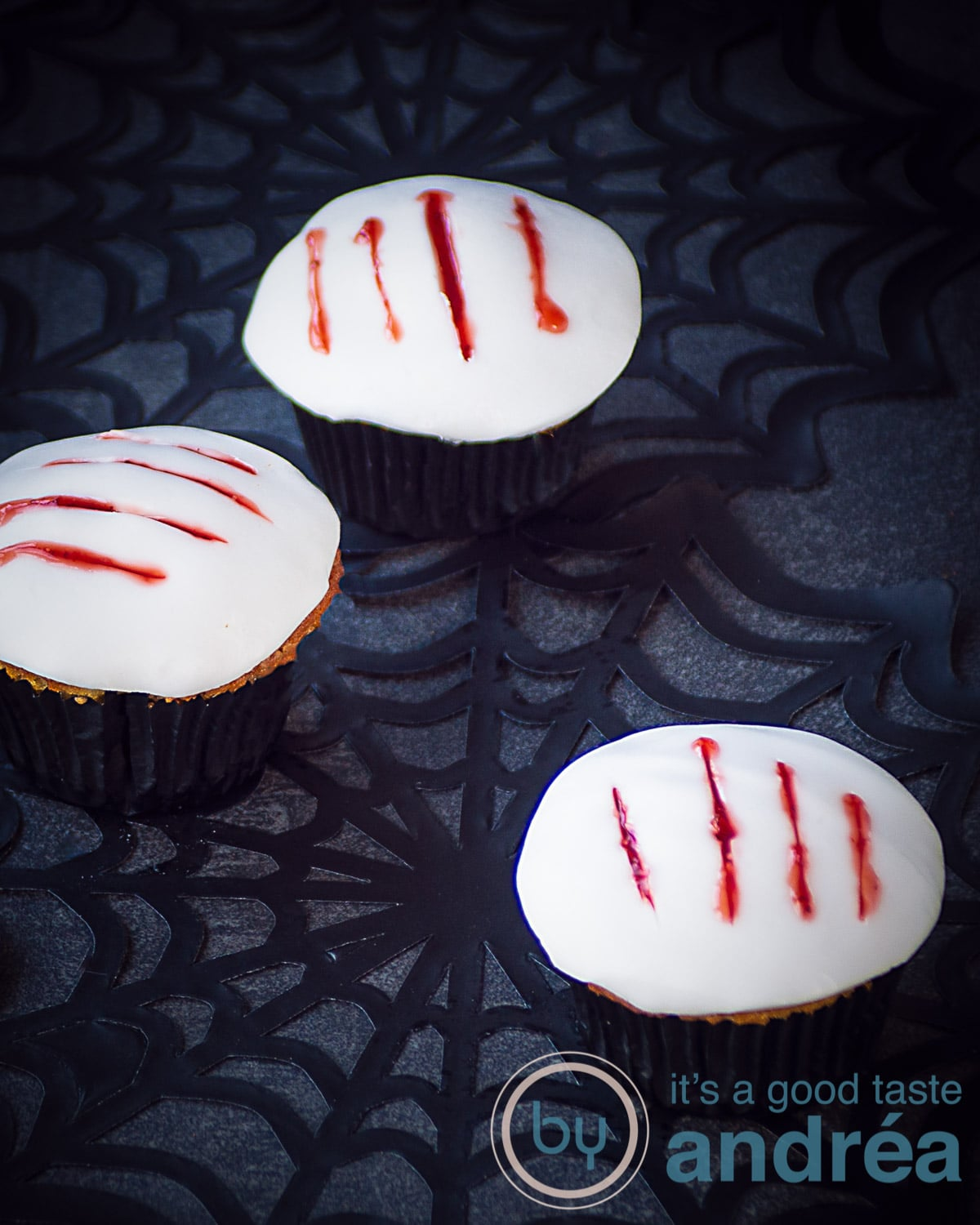 Three cupcakes with a white topping and some claw marks filled with strawberry blood. They're placed on cob webs