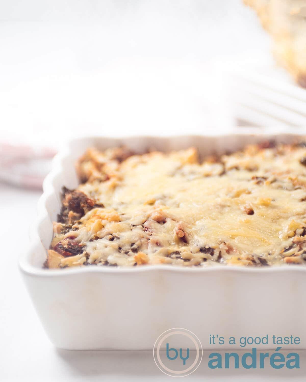 a white casserole dish filled with a kale potato gratin
