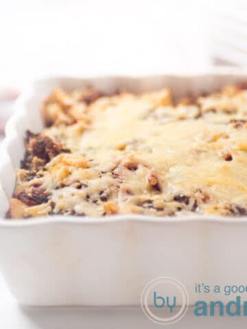 a square photo of half a casserole dish filled with kale gratin with potatoes