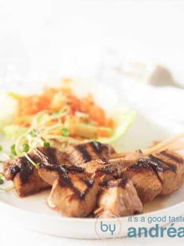 Pork tenderloin kebabs with a cucumber carrot salad on a plate