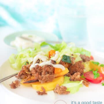 A white plate with potatoes, minced beef, iceberg lettuce garnished with tomato and garlic sauce