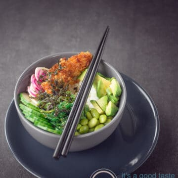 A gray bowl filled with cucumber, sriracha, lima beans, avocado and beets. Topped with seaweed.