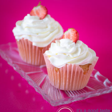 two strawberry cupcakes on a glass plate